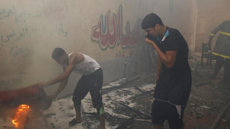 Palestinians attempt to put out a fire at the scene of what witnesses said was an Israeli air strike on a house in Gaza City