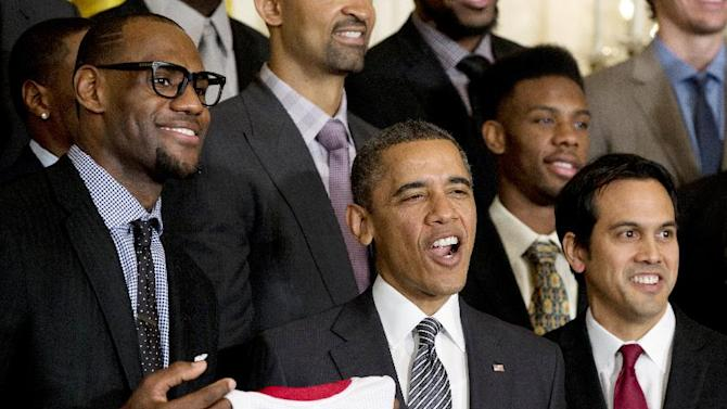 President Barack Obama is flanked by Miami Heat forward LeBron James, left, and coach Erik Spoelstra, right, as he welcomes the NBA basketball champion Miami Heat, to the East Room of the White House, Monday, Jan. 28, 2013, in Washington. (AP Photo/Carolyn Kaster)