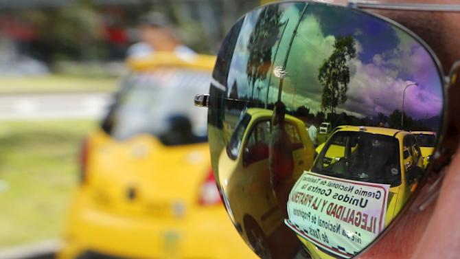 Cabs are reflected in sunglasses as cab drivers block an avenue to protest against the Uber ride sharing service in Bogota