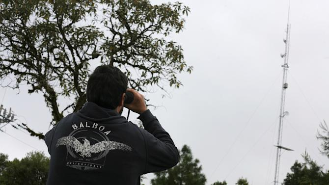 Peter Bloom, founder of non-profit group Rhizomatica, uses a pair of binoculars to observe an antenna of the community-run phone network in Santa Maria Yaviche