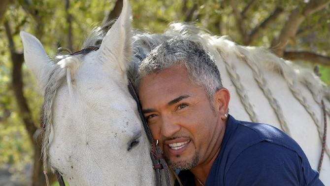 "In this Oct. 18, 2012 photo, Cesar Millan poses with his horse Conquistador at his Dog Psychology Center, in Santa Clarita, Calif. Millan has a new television show, book, tour and documentary. ""Cesar Millan: The Real Story"" airs on Nat Geo Wild on Nov. 25, 2012. It will also launch a global speaking tour. (AP Photo/Mark J. Terrill)"