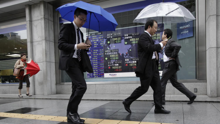 Men check their mobile phones as they walk by an electronic stock indicator in Tokyo Tuesday, May 15, 2012. Asian stock markets were mostly lower Tuesday, rattled by a political impasse in Greece that could lead the debt-stricken country to a destabilizing exit from the euro currency union. Japan's Nikkei 225 index fell 73.10 points, or 0.81 percent, to close at 8,900.74, a new three-month low. (AP Photo/Shizuo Kambayashi)
