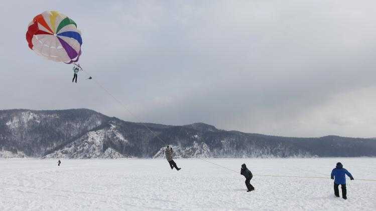 Men hold onto a cord attached to a girl's parachute on the frozen surface of the Yenisei River in taiga district