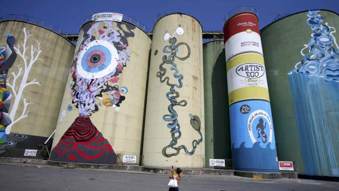 A woman takes a photo of colourfully painted silos called 'Street Art silos' which are part of an art festival at the harbour of Catania