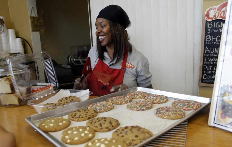 In this Tuesday, July 2, 2013 photo, Carrie Jackson packs freshly baked cookies at her business, the Original Cookie Lady, in the Village West neighborhood of Coconut Grove in Miami. Jackson has been in business since 1982, but has seen the neighborhood suffer from decline and lack of investment. (AP Photo/Lynne Sladky)