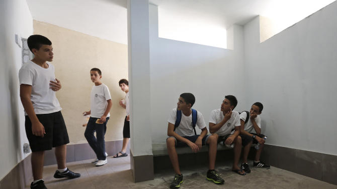Israeli high-school students gather in a fortified shelter next to a new rocketproof school building, in Shaar Hanegev school, near the southern town of Sderot, Israel, Monday, Aug. 27, 2012. The 27.5 million US Dollar structure features concrete walls, reinforced windows and a unique architectural plan all designed specifically to absorb rocket fire. (AP Photo/Tsafrir Abayov)