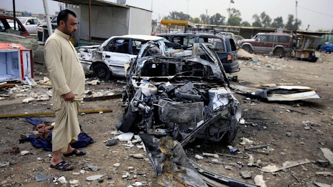 An Iraqi man inspects the aftermath of a car bomb attack at a used cars dealers parking lot in Habibiya neighborhood of eastern Baghdad, Iraq, Tuesday, April 16, 2013. Less than a week before Iraqis in much of the country are scheduled to vote in the country's first elections since the 2011 U.S. troop withdrawal, a series of attacks across Iraq on Monday, many involving car bombs, has killed and wounded dozens of people, police said. (AP Photo/ Karim Kadim)