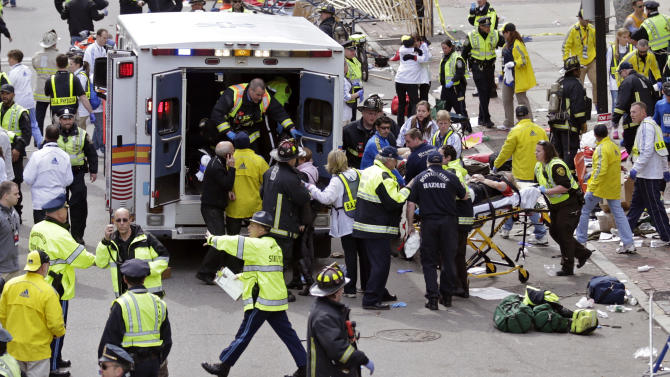Medical workers aid injured people at the finish line of the 2013 Boston Marathon in Boston, Monday, April 15, 2013. Two bombs exploded near the finish line of the Boston Marathon on Monday, killing at least two people and injuring dozens of others (AP Photo/Charles Krupa)