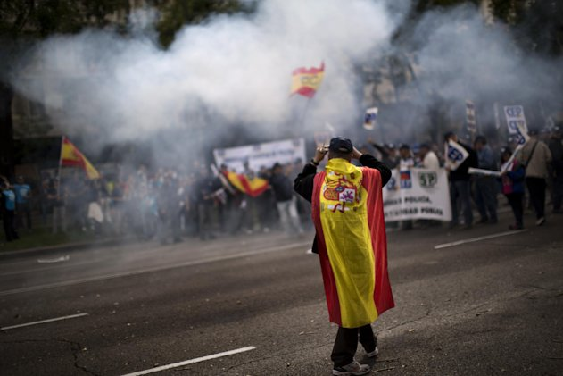 A police officer wearing an Spanish flag walks in front of a demonstration where other police officers protest as they block the street and light firecrackers next to the Interior Ministry in Madrid, Spain, Saturday, Oct. 27, 2012. The demonstrators were protesting parts of the austerity package, namely the elimination of one of 14 paychecks that most Spanish civil servants get each year. The one being axed comes right before Christmas. (AP Photo/Emilio Morenatti)