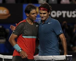 Rafael Nadal of Spain and Roger Federer of Switzerland hug at the net, after Nadal won their men's singles semi-final match at the Australian Open 2014 tennis tournament in Melbourne