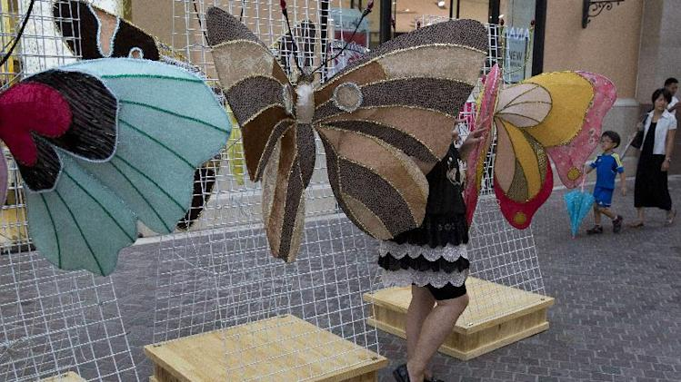 A woman poses for photos between butterfly installations at a mall in Beijing, China, Thursday, Aug. 28, 2014. Mall operators routinely display art works to increase the flow of visitors as a way to boost sales of retail tenants. (AP Photo/Ng Han Guan)