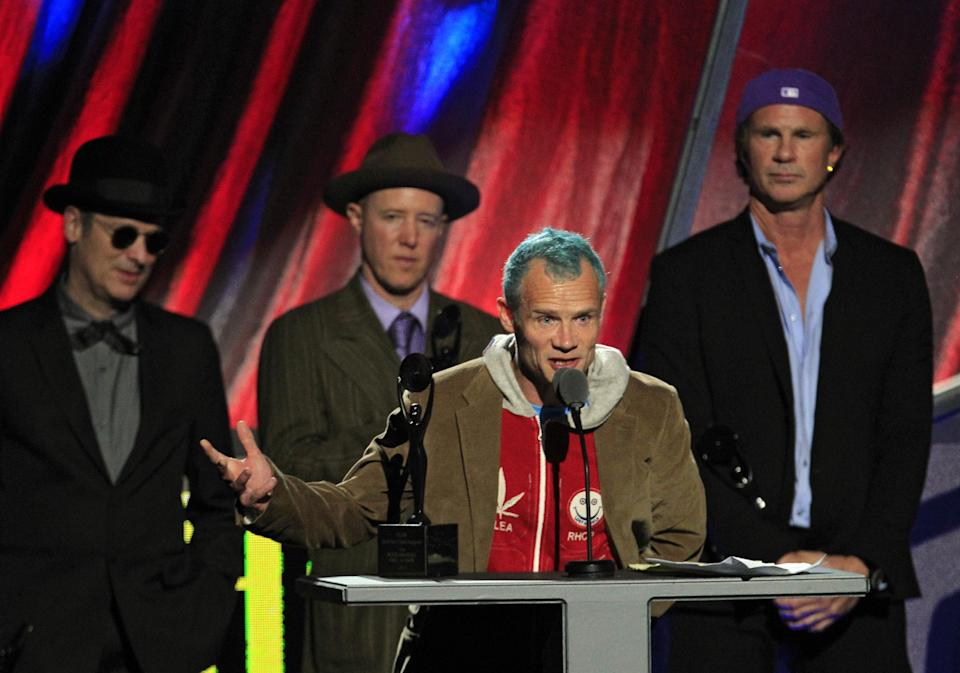 "Red Hot Chili Peppers'  Mike ""Flea"" Balazary speaks after induction into the Rock and Roll Hall of Fame Sunday, April 15, 2012, in Cleveland. Former drummers Cliff Martinez, far left, and Jack Irons, join current drummer Chad Smith, right. (AP Photo/Tony Dejak)"