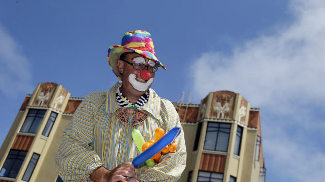 """Kenny the Clown,"" otherwise known as Kenneth Kahn, smiles as he hands out balloons in San Francisco, Friday, Aug. 17, 2012. Kahn says he unwittingly received a stolen iPad from a friend who was later arrested for breaking into former Apple CEO Steve Jobs' residence in Palo Alto. Kahn said he had the stolen iPad for a few days before police came asking for the purloined tablet, which was returned to the Jobs family. The professional entertainer said he never examined the device's contents. Instead he downloaded the ""Pink Panther"" and other songs to play while entertaining kids and tourists during his clown routine. Kahn said had no idea where the 64GB iPad came from until his friend, 35-year-old Kariem McFarlin of Alameda, Calif., was arrested Aug. 2. (AP Photo/Marcio Jose Sanchez)"