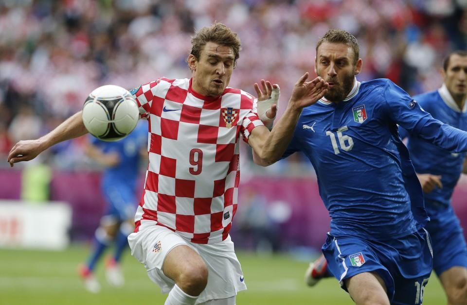 Croatia's Nikica Jelavic, left, and Italy's Daniele De Rossi fight for the ball during the Euro 2012 soccer championship Group C match between Italy and Croatia in Poznan, Poland, Thursday, June 14, 2012. (AP Photo/Gregorio Borgia)