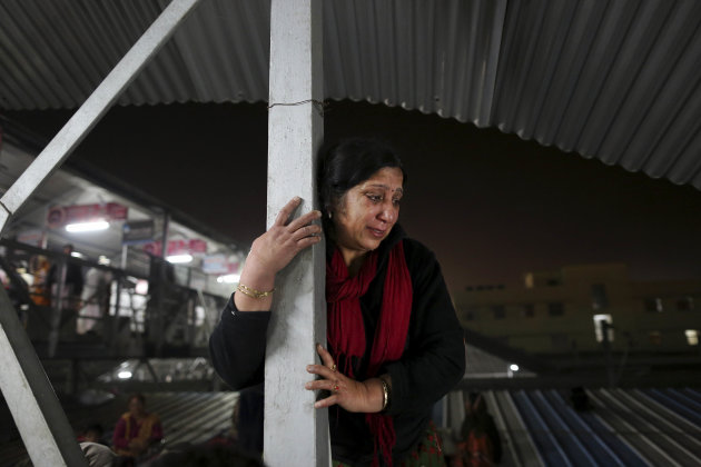 An Indian woman weeps as she watches from a staircase as rescue workers tend to the bodies of those killed in a stampede on a railway platform at the main railway station in Allahabad, India, Sunday,