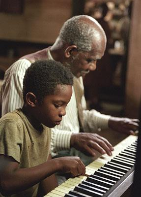 C.J. Sanders as young Ray Charles and Robert Wisdom as Jack Lauderdale in Universal's Ray