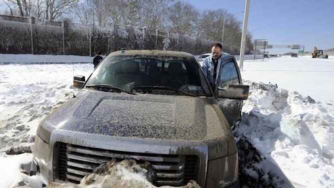 Wayne Gingo, of Medford, N.Y., gets back into his car that got stuck in the snow on the Long Island Expressway eastbound near Exit 60, Saturday, Feb. 9, 2013, in Ronkonkoma, N.Y. Gingo was driving home from his job as a postal worker at JFK Airport and got stuck in the snow at 1:45 a.m. He spent the night in the car waiting for a tow truck. (AP Photo/Kathy Kmonicek)