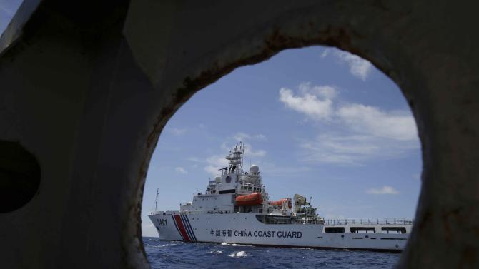 A China Coast Guard vessel attempts to block a Philippine government vessel as the latter tries to enter the China Second Thomas Disputed Shoals (local name Ayungin Shoal) to replace Philippine troops and resupply provisions Saturday, March 29, 2014 off the South China Sea. Chinese coast guard ships set up a blockade but a lone Philippine boat maneuvered past them in the high seas Saturday to deliver a fresh batch of Filipino troops and food supplies to a disputed shoal in a tense, cat-and-mouse-like confrontation witnessed for the first time by journalists in the South China Sea. (AP Photo/Bullit Marquez)