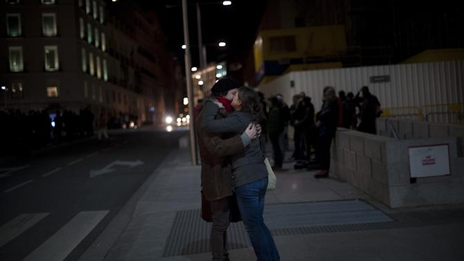 Two people kiss outside the Parliament as the Spanish Parliament considers whether to admit a popular petition to change mortgage laws and halt evictions of those unable to pay mortgages to a vote in Madrid, Tuesday, Feb. 12, 2013. The government agreed to consider changes to the law on mortgages after pressure from opposition parties and a growing public outcry, including a petition that was signed by 1.4 million people – enough signatures to force Parliament to discuss alterations to the law in a special session. (AP Photo/Daniel Ochoa de Olza)