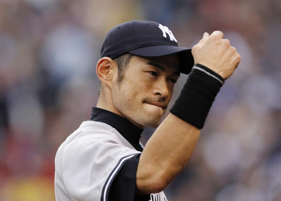New York Yankees right fielder Ichiro Suzuki readies for a fist bump as he heads into the dugout after catching a fly ball from Seattle Mariners' Kyle Seager to end the first inning of a baseball game Monday, July 23, 2012, in Seattle. (AP Photo/Elaine Thompson)