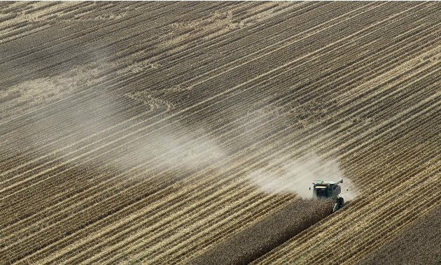 FILE - In this Aug. 16, 2012 file photo, dust is carried by the wind behind a combine harvesting corn in a field near Coy, Ark. A brutal combination of a widespread drought and a mostly absent winter