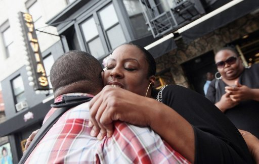Melba Wilson (C), niece of famed restaurateur Sylvia Woods, hugs a well wisher