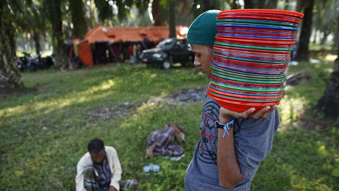 A Rohingya migrant, who arrived in Indonesia this week by boat, collects plates from breakfast at a temporary shelter in Aceh Timur