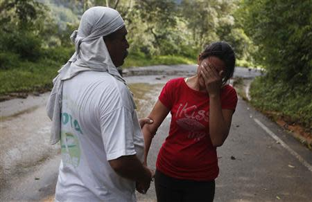 A woman, who lost her daughter in a mudslide, is comforted by a resident near the village of El Paraiso, in the Mexican state of Guerrero