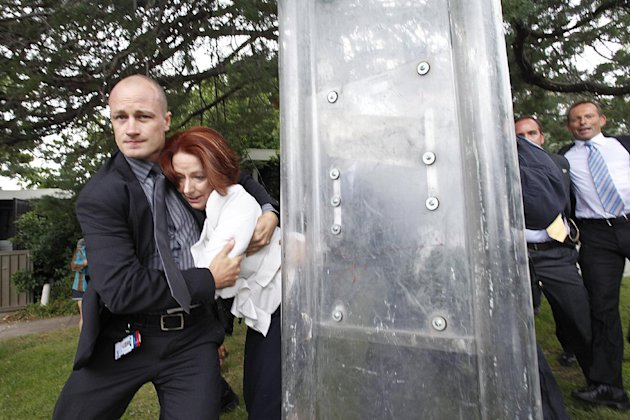 Prime Minister Julia Gillard, second from left, is escorted out for safety by body guards and police through a crowd of rowdy protesters following a ceremony to mark Australia's national day in Canber