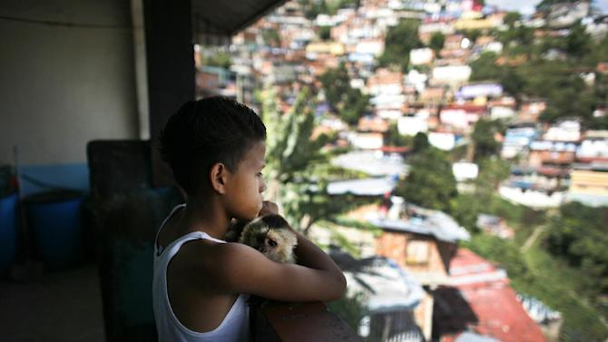 """In this June 1, 2012 photo, Miguel Uzcategui,13, embraces his pet monkey named, """"Fabiola,"""" as he looks out from his home in the San Agustin slum in Caracas, Venezuela. Every weekend, boys line up with their gloves to slug it out in a boxing ring that moves around Caracas from parks to plazas to streets in the slums. They're participating in a program supported by the Venezuelan government that aims not only to develop standout fighters but also to expand the sport's reach and give poor teenagers an outlet to stay away from crime, alcohol and drugs. Uzcategui says the sport has given him goals as well as improved self-confidence. (AP Photo/Ariana Cubillos)"""