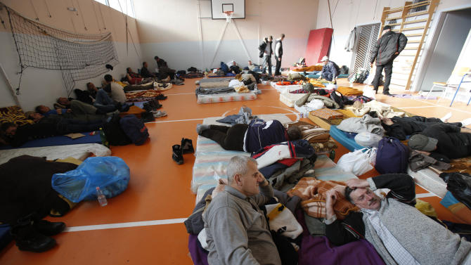 Bosnian workers rest, after marching all night,  in an elementary school sports hall , as they reach the city of Orasje, on the border with Croatia,  250 kms north of Sarajevo on Saturday, Dec. 27, 2014. Nearly 200 employees of Bosnian factories that have closed, leaving them without pay for more than a year, are marching toward Croatia in the hope of getting jobs there. The workers left  city of Tuzla in northern Bosnia on a journey of 77 kilometers (47 miles) to the Croatian border. Croatia, a European Union country, is more prosperous than Bosnia, where unemployment is more than 40 percent. Bosnia's transition to capitalism and a market economy, which began two decades ago, included the privatization of state-owned factories, but many of them have gone bankrupt. Existing laws prevent many of the workers from being laid off, but they often don't get paid. (AP Photo/Amel Emric)