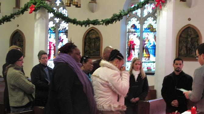 Relatives and others remember Latief Anderson during a vigil at Cathedral of the Immaculate Conception in Camden, N.J., on Dec. 31, 2012. Anderson was one of a record 67 homicide victims in the city of 77,000 in 2012. (AP Photo/Geoff Mulvihill)