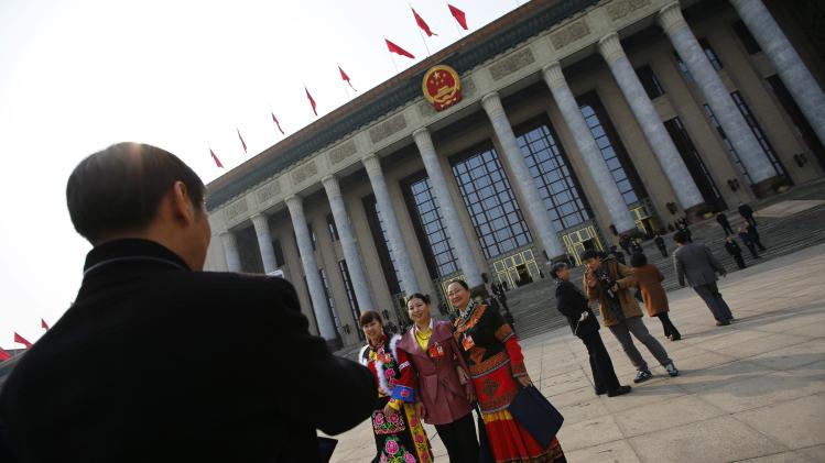 Ethnic minority delegates pose for pictures outside the Great Hall of the People during the third plenary session of the National People's Congress in Beijing