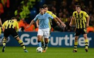 Manchester City's Argentinian forward Sergio Aguero (C) looks for a way through the Dortmund defence during the UEFA Champions League football match between Manchester City and Borussia Dortmund at the Etihad stadium, in Manchester. The match ended in a 1-1 draw