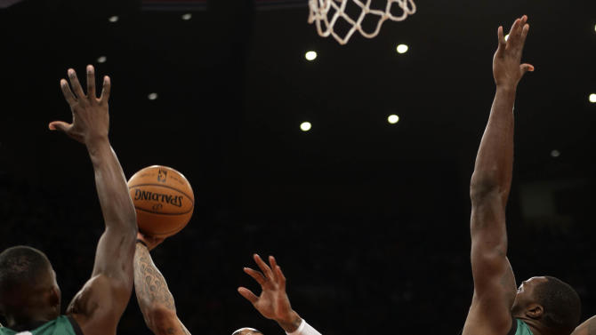 New York Knicks' J.R. Smith, center, puts up a shot past Boston Celtics defense during the first half of an NBA basketball game at Madison Square Garden Sunday, March 31, 2013 in New York.  (AP Photo/Seth Wenig)