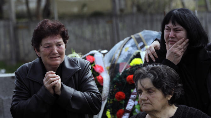 People react prior to a mass funeral of the victims of a shooting in the village of Velika Ivanca, some 50 kilometers (30 miles) southeast of Belgrade, Serbia, Friday, April 12, 2013. The village  is preparing for the funerals of thirteen victims of a shooting that happened on Tuesday, April 9, 2013. Ljubisa Bogdanovic, a local and a Yugoslav wars veteran, went from house to house on April 9 in the village at dawn, cold-bloodedly gunning down his mother, his son, a 2-year-old cousin and ten other neighbors. (AP Photo/ Darko Vojinovic)
