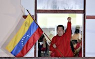 "Venezuelan President Hugo Chavez waves a Venezuelan flag while speaking to supporters after receiving news of his reelection in Caracas on October 7. Chavez pledged to become a ""better president"" and work with the opposition after winning a tough re-election battle that betrayed simmering discontent at his socialist revolution"