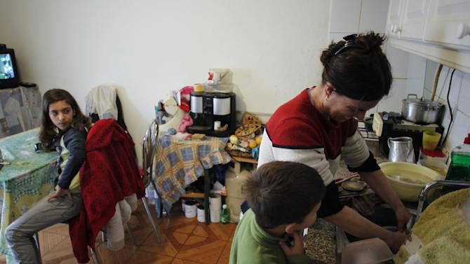 In this photo taken on March 29, 2013, Elena Baptista, right, prepares a meal with her daughter Vania, 12, left, and son Joao, 7, in their house's kitchen/living room in Loures, outside Lisbon. The Baptista family counts itself among the casualties of an unrelenting financial crisis that is squeezing the life out of some European Union economies, including Portugal. Pedro Baptista, a stocky 37-year-old, has found work as a part-time window cleaner but his wife Elena, 35, has been on unemployment benefit for almost a year after losing her job in a school canteen. (AP Photo/Francisco Seco)