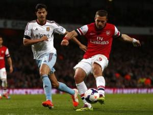 Arsenal's Podolski scores his second goal against West Ham United during their English Premier League soccer match at the Emirates stadium in London