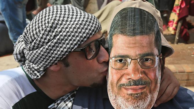 """A supporter of Egypt's ousted President Mohammed Morsi, left, kisses his friend with Morsi's mask during a demonstration before the Friday prayer in Nasr City, Cairo, Egypt, Friday, July 12, 2013. Thousands of supporters of Egypt's Muslim Brotherhood group rallied in a Cairo city square, waving pictures of the ousted president and chanting anti-military slogans, deriding army chief who led Morsi's removal as """"traitor"""" with one ultraconservative Salafi cleric vows to stay in the streets for years until Morsi is reinstated. (AP Photo/Hussein Malla)"""