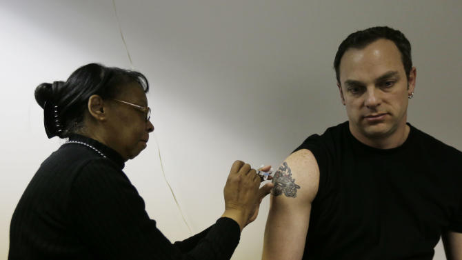Pam Horn administers the flu vaccine to employee Michael Karolitzky at Philly Flu Shots on Thursday, Jan. 10, 2013, in Philadelphia. The flu season arrived early in the U.S. this year, but health officials and experts say it's too early to say this will be a bad one. Experts say evidence so far is pointing to a moderate flu season - it just looks worse because last year's season was so mild. Flu usually doesn't blanket the country until late January or February. Now, it's already widespread in more than 40 states. That could change when the next government report comes out Friday. (AP Photo/Matt Rourke)