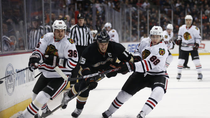 Anaheim Ducks' Ryan Getzlaf, center, fights for the puck with Chicago Blackhawks' Dave Bolland, left, and Patrick Kane during the first period of an NHL hockey game in Anaheim, Calif., Wednesday, March 20, 2013. (AP Photo/Jae C. Hong)