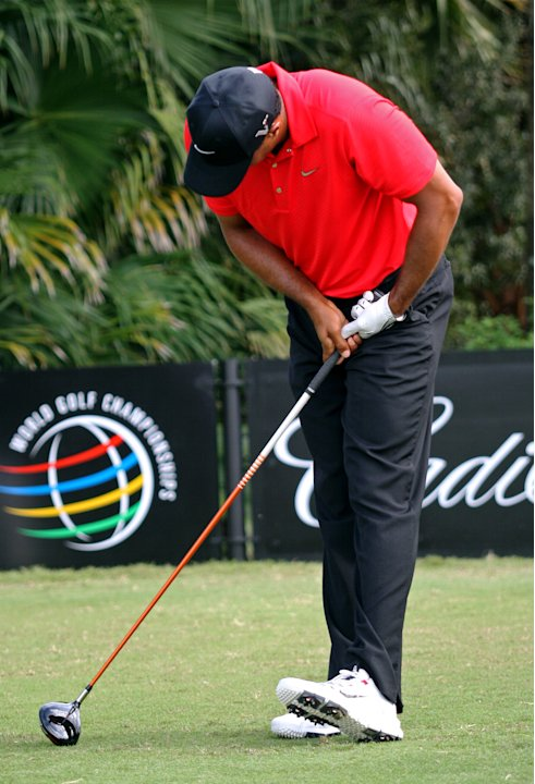 Tiger Woods grimaces after hitting from the 12th tee during the final round of the Cadillac Championship golf tournament on Sunday, March 11, 2012 in Doral, Fla. Woods the withdrew from the tournament
