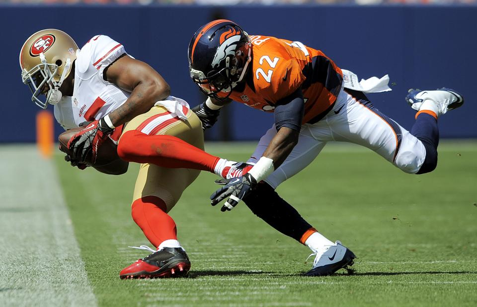 San Francisco 49ers wide receiver Michael Crabtree (15) catches a pass in front of Denver Broncos defensive back Tracy Porter (22) during the first quarter of an NFL preseason football game in Denver, Sunday, Aug. 26, 2012. (AP Photo/Jack Dempsey)