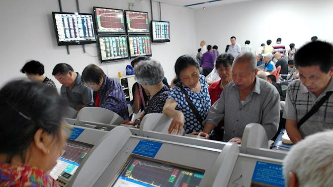 Investors look over stock prices on display terminals at a brokerage house in Yichang in central China's Hubei province, Monday, May 25, 2015. China's Shanghai Composite Index surged 3.4 percent to 4,813.80 on Monday as Asian stocks were mostly higher on a quiet trading day with Hong Kong, Wall Street and London closed for holidays. (Chinatopix Via AP) CHINA OUT
