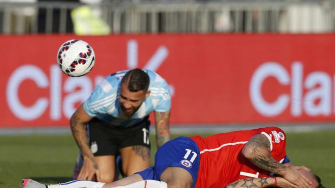 Chile's Vargas reacts after being tackled by Argentina's Otamendi during their Copa America 2015 final soccer match at the National Stadium in Santiago
