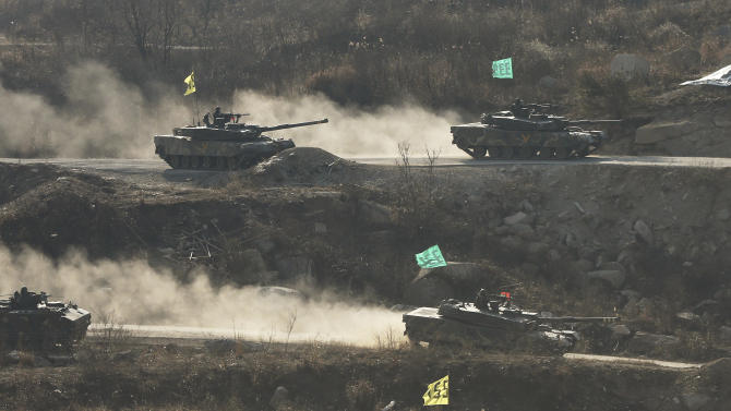 South Korean army K1 tanks move during an exercise at Seungjin Fire Training Field in mountainous Pocheon, South Korea, near the border with North Korea, Wednesday, March 27, 2013. North Korea said Wednesday that it had cut off a key military hotline with South Korea that allows cross border travel to a jointly run industrial complex in the North, a move that ratchets up already high tension and possibly jeopardizes the last major symbol of inter-Korean cooperation. (AP Photo/Yonhap, Lim Byung-shick)  KOREA OUT