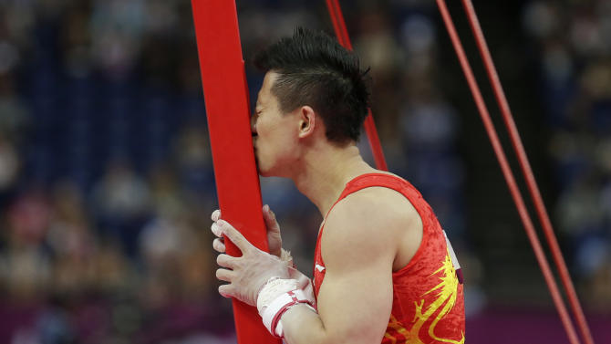 Silver medallist China's Chen Yibing kisses the bar after his performance on the rings during the artistic gymnastics men's apparatus finals at the 2012 Summer Olympics, Monday, Aug. 6, 2012, in London. (AP Photo/Gregory Bull)