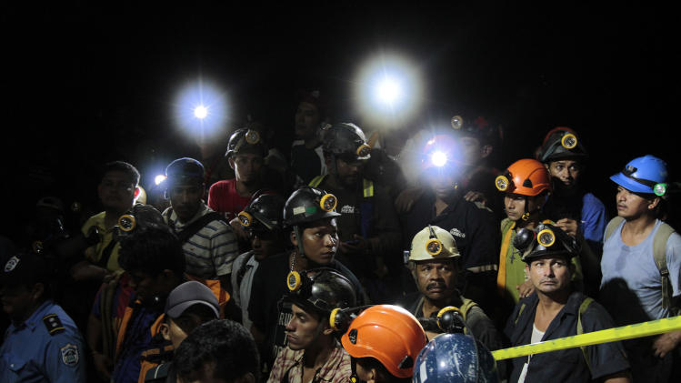 Miners stand at the entrance as they wait to hear about the rescue of fellow miners trapped in a gold mine blocked by a landslide in Bonanzas town