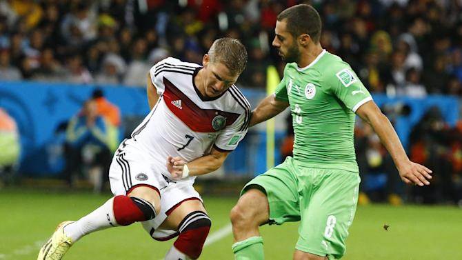 Germany's Schweinsteiger fights for the ball with Algeria's Lacen during extra time in their 2014 World Cup round of 16 game at the Beira Rio stadium in Porto Alegre